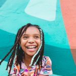 young girl smiles in from of blue and orange mural wall Rosemont PA Lucy Baber Top Family Photographer