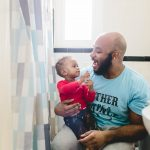 dad holds toddler child in bathroom while brushing teeth Philly family photographer Lucy Baber