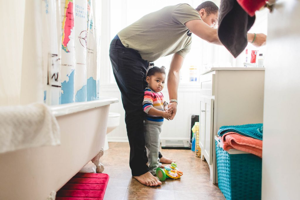 father helps toddler daughter in bathroom at home Fishtown Philadelphia Lucy Baber Family Photographer