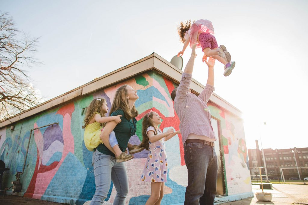 parents with their three young children by mural wall in park Main Line PA Lucy Baber Family Photographer