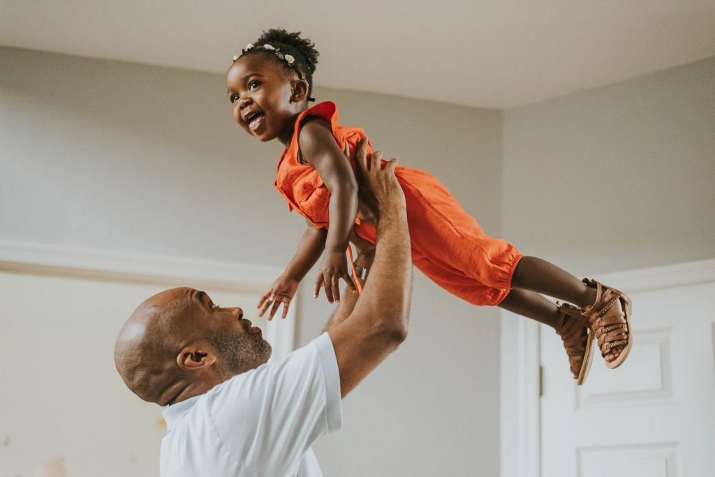 father lifts toddler daughter up in the air Chestnut Hill Philadelphia Lucy Baber Family Photographer