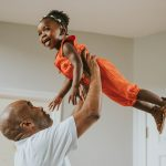 Black dad lifts smiling daughter up in home photo session Main Line PA Lucy Baber Photography