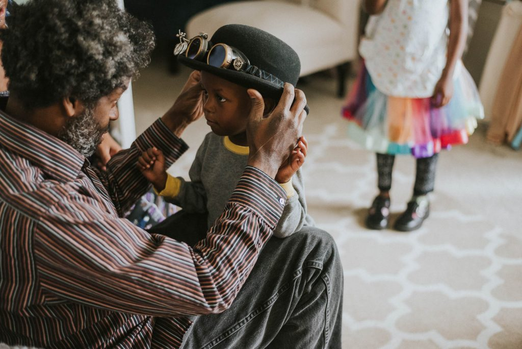 father helps toddler son and daughter play dress up at home Philadelphia Lucy Baber Family Photographer