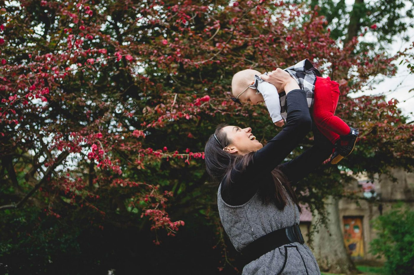 Mom lifts infant child up in air during autumn family photo session Philadelphia Lucy Baber Photography