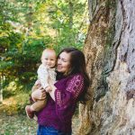 New mom holds infant baby by tree in park during autumn family photo session Philadelphia Lucy Baber Photography