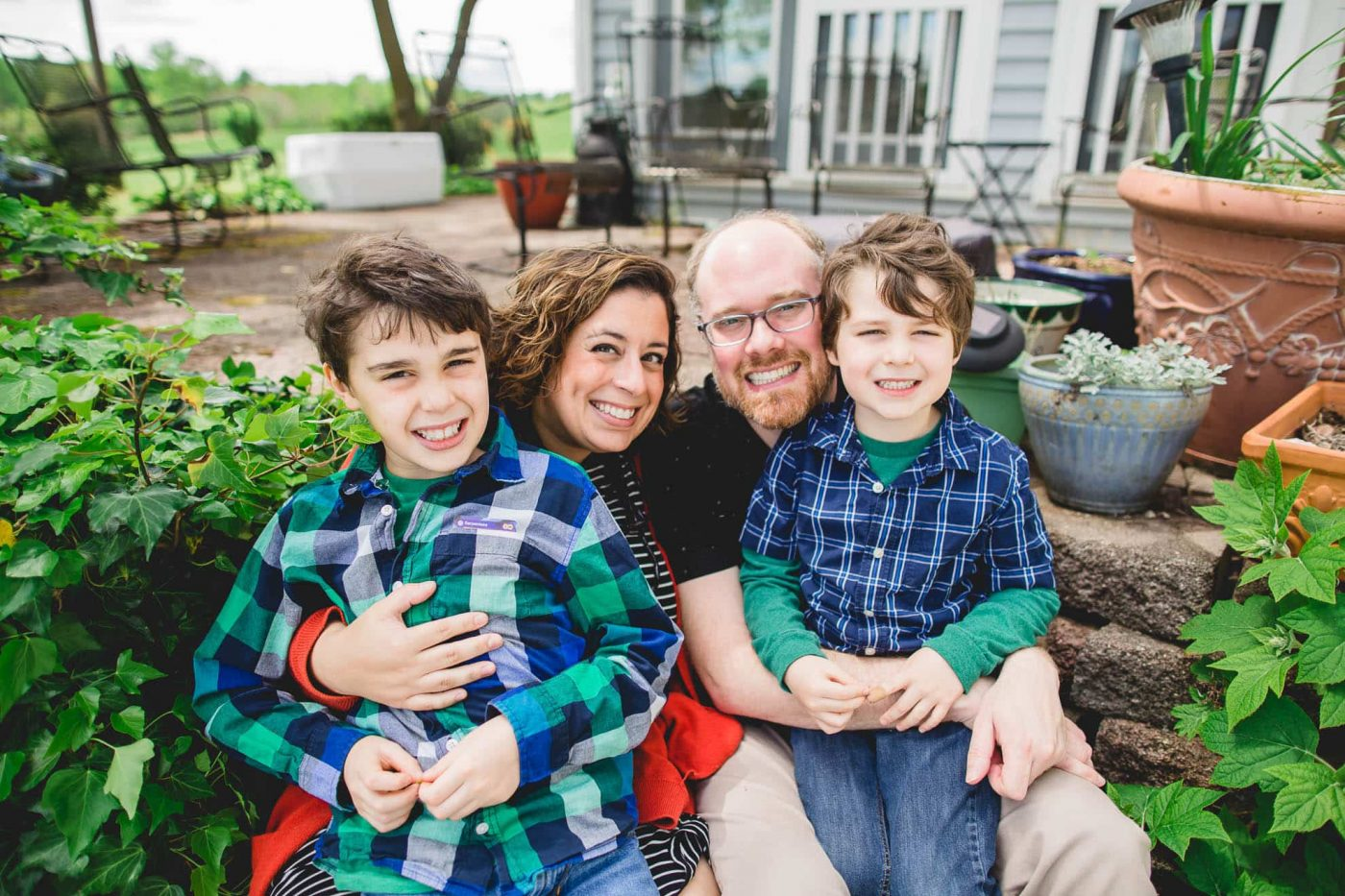 Family photo of Lucy Baber with her husband and two boys in their backyard Philadelphia