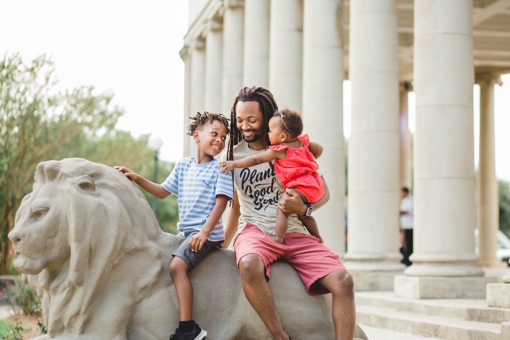 Black father with two kids sitting on a lion