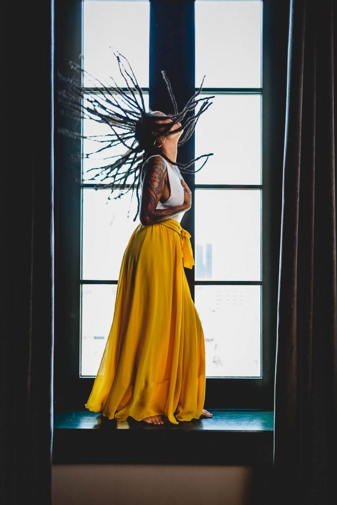Black woman yellow skirt dreadlocks